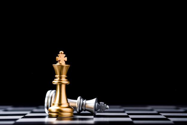 Stand des goldenen königschachs und des gefallenen silbernen königschachs auf dem schachbrett. gewinner des geschäftswettbewerbs und des planungskonzepts für marketingstrategien. Premium Fotos