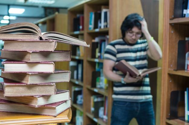 Stapel altes buch auf dem schreibtisch in der bibliothek mit dem mann, der über dem buchunschärfehintergrund liest Premium Fotos