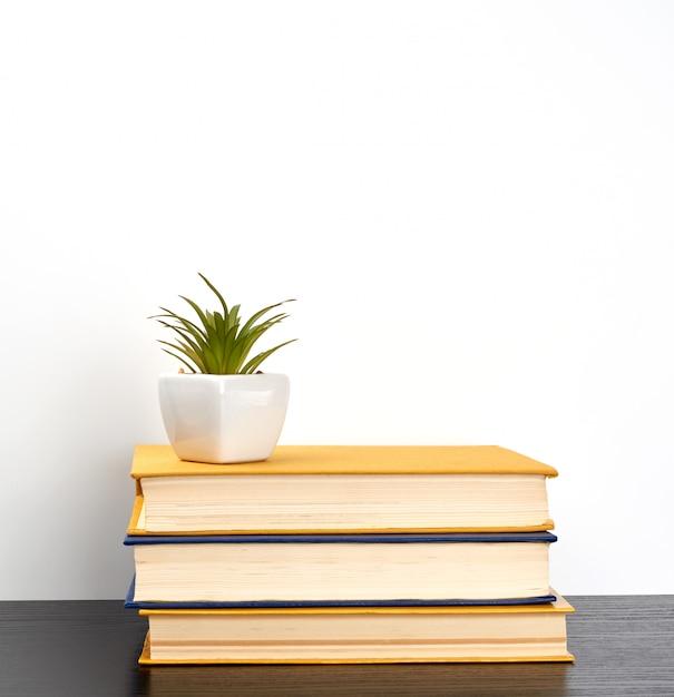Stapel bücher auf einem schwarzen tisch, auf einen keramiktopf Premium Fotos