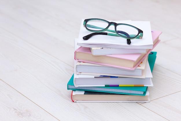 Stapel bücher mit brille an der spitze. konzept ursache für weitsichtigkeit, kurzsichtigkeit. Premium Fotos