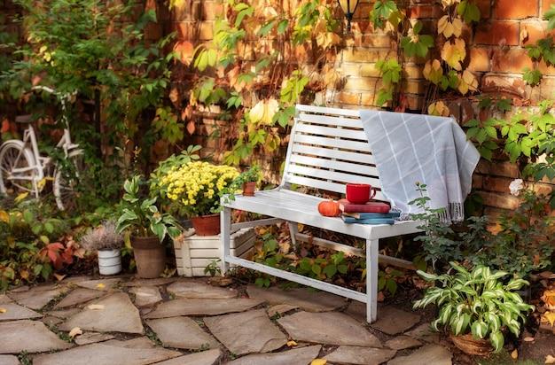 Stapel bücher, tasse tee, plaid und kürbis liegen auf holzbank im garten. dekor herbsthof Premium Fotos