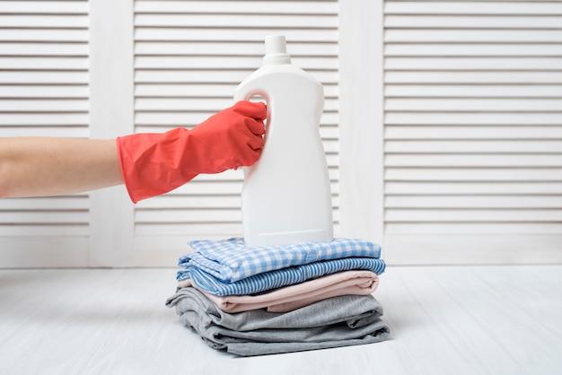 Stapel der gefalteten kleidung und der reinigungsmittelflasche in der weiblichen hand. hausarbeit Premium Fotos