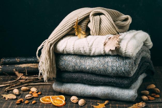 Stapel der winterstrickjacken mit blättern Kostenlose Fotos
