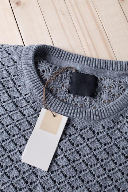 Stapel der wolle strickte warme strickjacke und des weißen aufklebers für text Premium Fotos