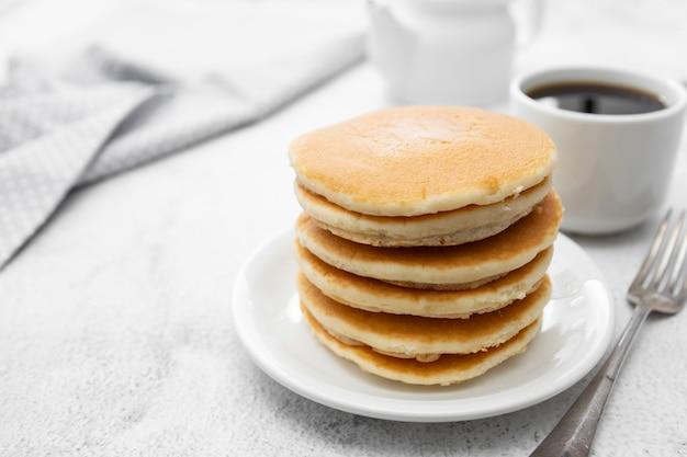 Stapel des amerikanischen clasic pfannkuchenfrühstücks oder -imbisses, getrennt auf weiß Premium Fotos