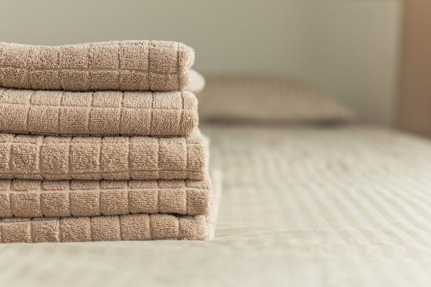 Stapel des beige hoteltuches auf bett im schlafzimmerinnenraum. vintage muskelaufbau Premium Fotos