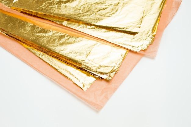 Stapel des quadratischen goldblattes auf weiß Premium Fotos