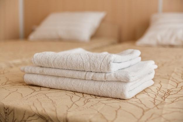 Stapel des weißen hoteltuches auf bett im schlafzimmerinnenraum. Premium Fotos