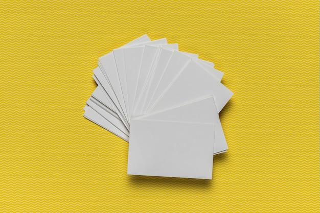 Stapel einladungen auf gelbem hintergrund Kostenlose Fotos