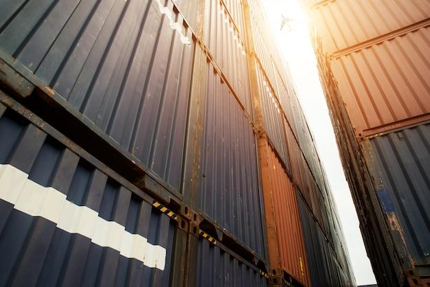 Stapel frachtbehälter am import- und exportbereich mit frachtflugzeug am hafen. Premium Fotos