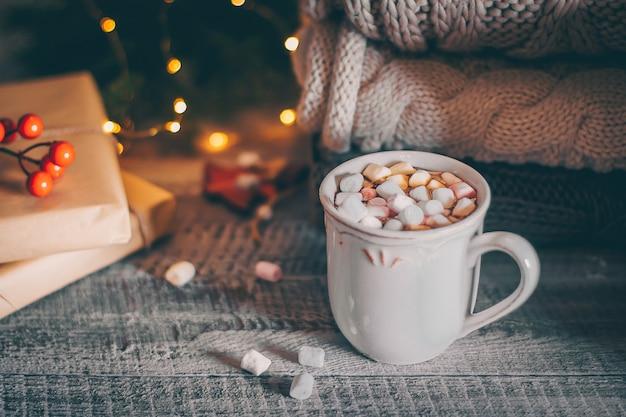 Stapel gemütliche gestrickte pullover und tasse heiße schokolade mit eibisch Premium Fotos
