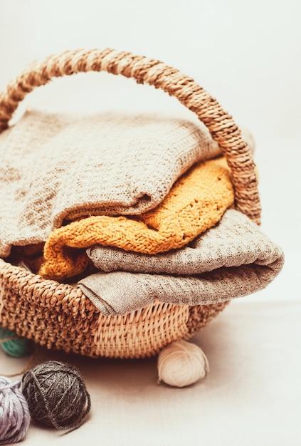 Stapel gemütliche gestrickte strickjacken im weidenkorb Premium Fotos