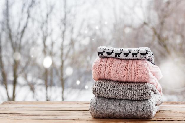 Stapel gestrickte kleidung auf holztisch auf winternatur ourdoor Premium Fotos
