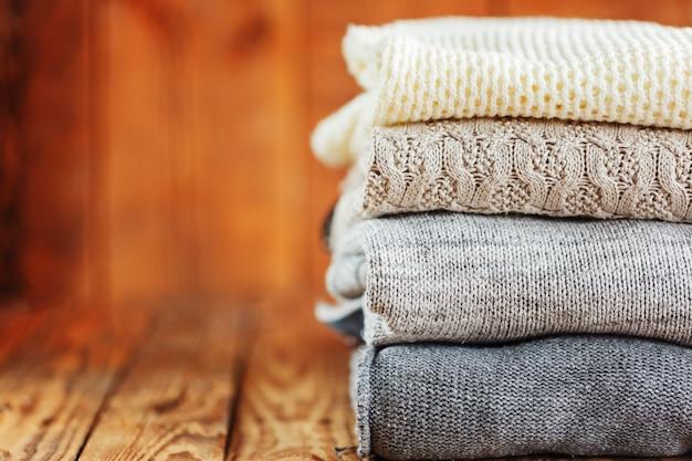 Stapel gestrickte winterkleidung auf hölzernem, strickjacken Premium Fotos