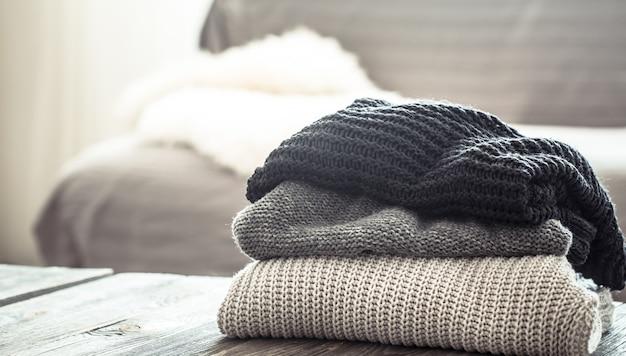 Stapel gestrickter pullover auf einem holztisch Kostenlose Fotos