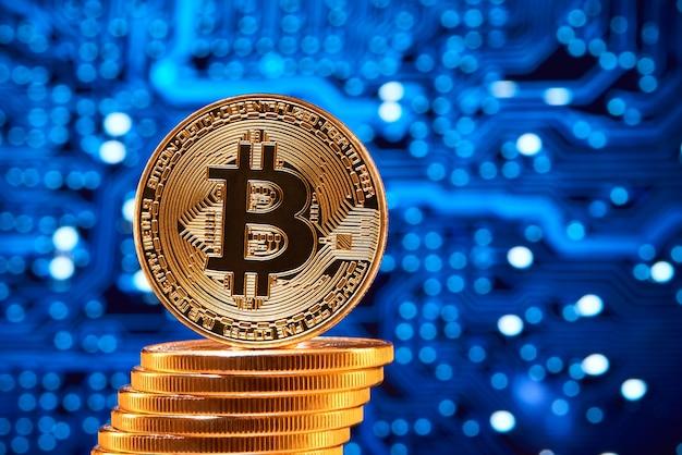 Stapel goldene bitcoins mit einem bitcoin auf seinem rand gesetzt auf unscharfen blauen stromkreis. Premium Fotos