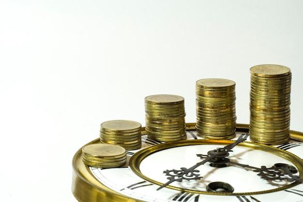 Stapel goldmünzen auf der uhr Premium Fotos