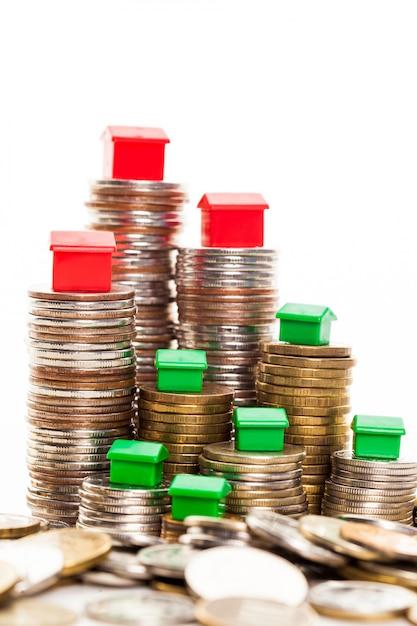 Stapel münzen, grünes und rotes haus. hypothekenkonzept durch geldhaus von den münzen Premium Fotos