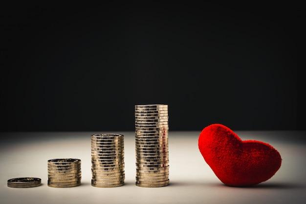 Stapel münzen und rotes herz Premium Fotos