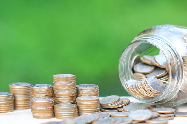 Stapel münzengeld und glasflasche auf natürlichem grün Premium Fotos
