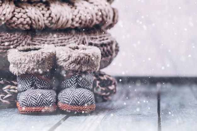 Stapel-stapel der gemütlichen gestrickten strickjacken auf einem holztisch. warmes konzept Premium Fotos