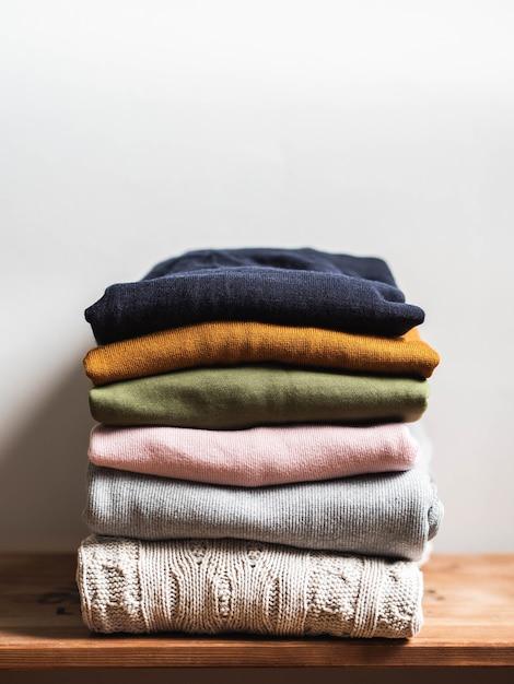 Stapel von bunten herbstkleidung auf einem hölzernen hintergrund, pullover, strickwaren, kopienraum Premium Fotos