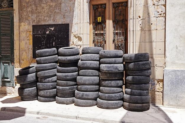 Stapel von gebrauchtwagengummireifen nahe selbstgarage auf straße. Premium Fotos