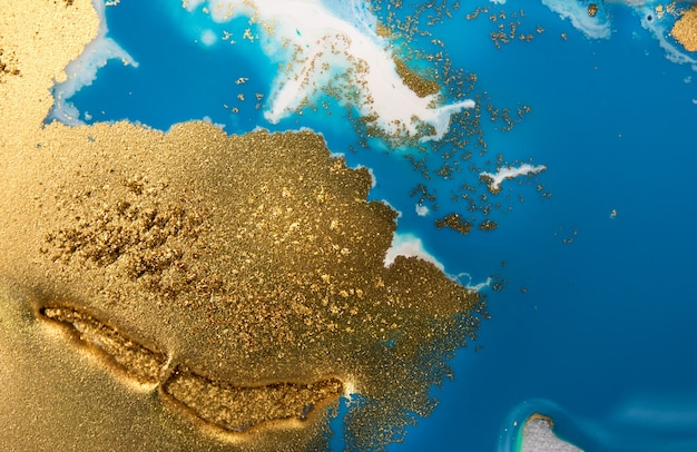 Stapel von goldenen pailletten auf blauen farbflecken. abstrakte gießende farbe Premium Fotos