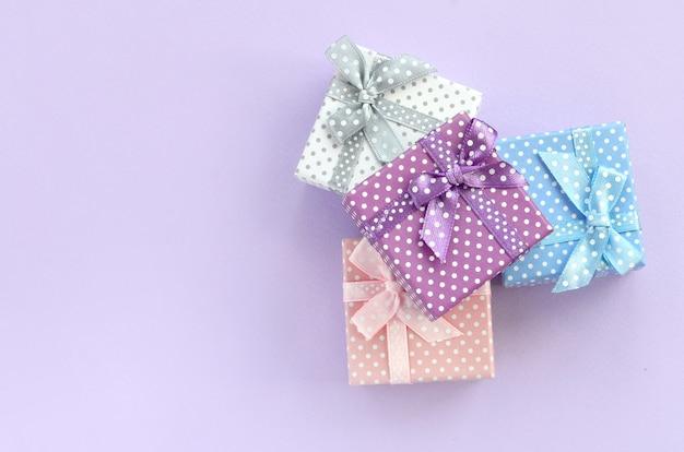 Stapel von kleine farbige geschenkboxen mit bändern liegt auf einem violetten hintergrund Premium Fotos