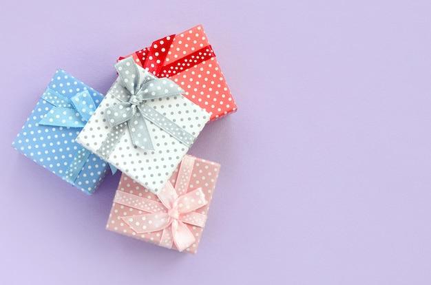 Stapel von kleinen farbigen geschenkboxen mit bändern liegt auf einem violetten hintergrund. Premium Fotos