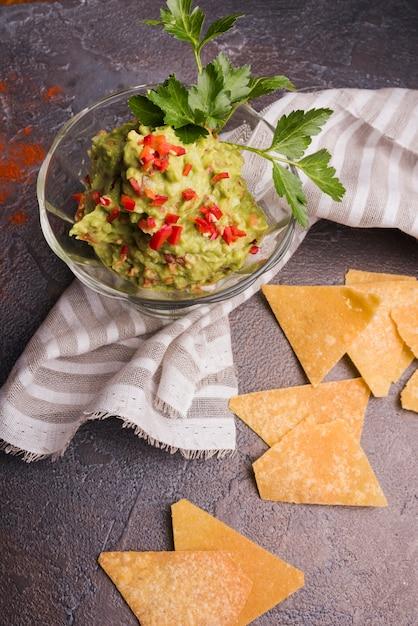 stapel von nachos in der n he von guacamole in sch ssel und serviette kostenlose foto