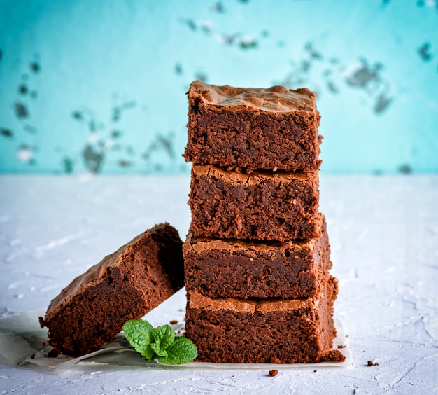 Stapel von quadratischen scheiben der gebackenen schokoladenkuchentorte Premium Fotos