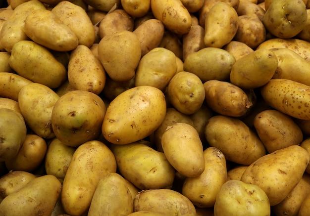 Stapel von ungekochten kartoffeln, mit selektivem fokus für hintergrund Premium Fotos