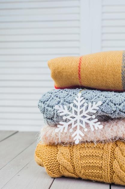 Stapel weiße gemütliche gestrickte strickjacken auf einem holztisch Premium Fotos
