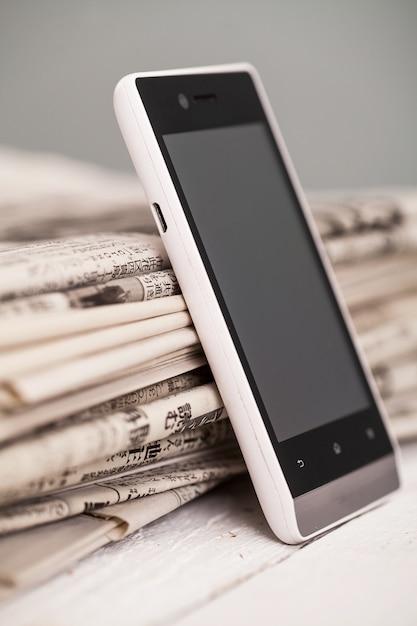 Stapel zeitungen mit smartphone drauf Kostenlose Fotos