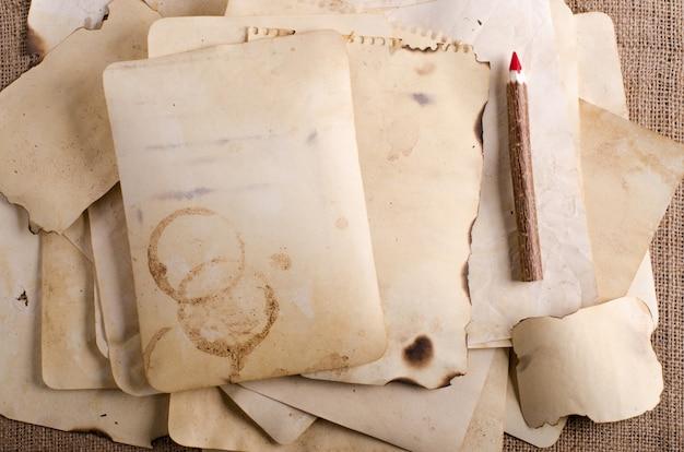 Stapeln sie alte papiere, notizbuch und hölzerne bleistifte auf leinwand, sackleinen. Premium Fotos