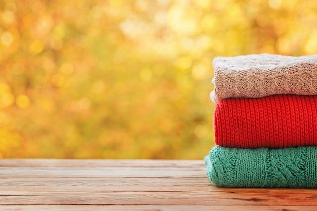 Stapelstapel der gestrickten herbstkleidung auf natur. Premium Fotos