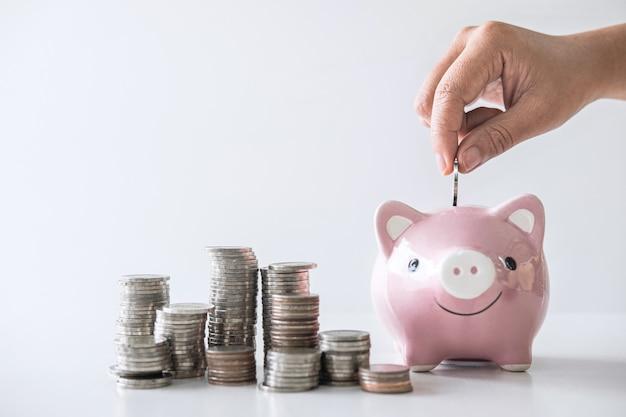 Stapelstapel und hand, die münze in sparschwein für die planung stecken, steigern zum wachsen Premium Fotos