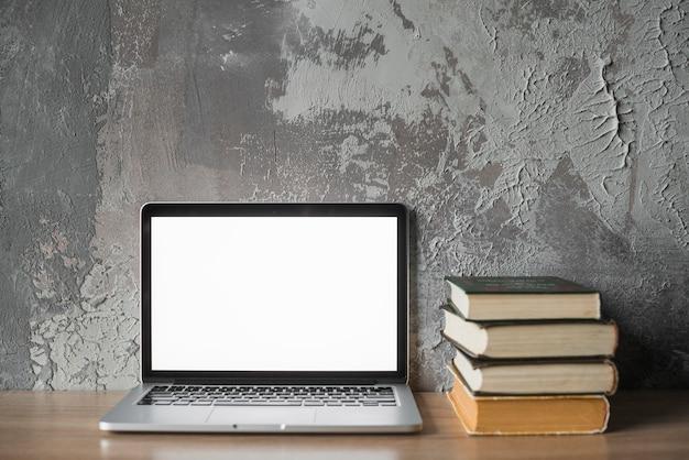 Staplungsbücher und laptop mit leerem weißem schirm auf holzoberfläche Kostenlose Fotos