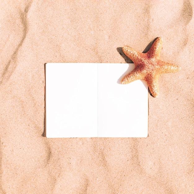Starfish auf sandhintergrund mit leerem notizbuch Kostenlose Fotos