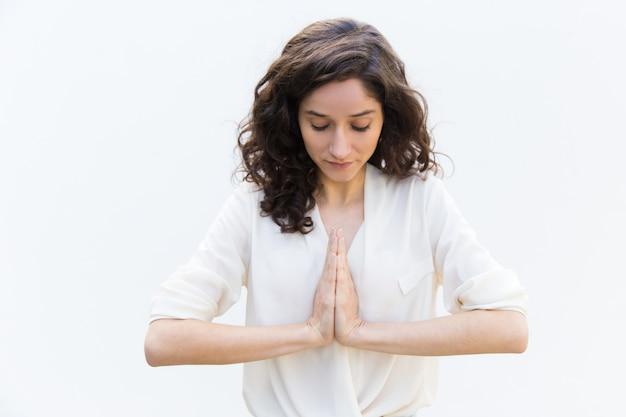 Starke frau, die mit den händen in namaste-geste meditiert Kostenlose Fotos