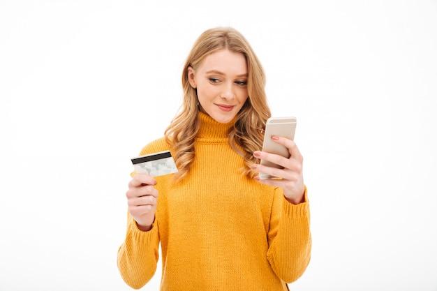 Starke junge frau, die handy und kreditkarte hält. Kostenlose Fotos