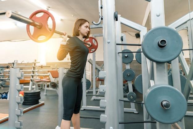 Starke junge frau, die schwergewichtstraining in der turnhalle tut Premium Fotos