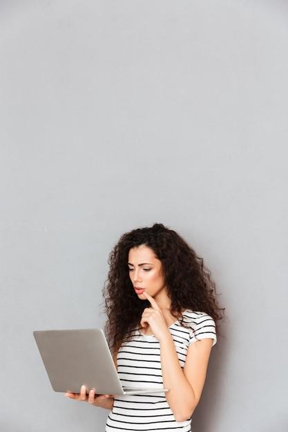 Starke studentin mit dem gelockten haar stehend mit notizbuch in den händen stark studierend oder interessantes ebook über grauer wand lesend Kostenlose Fotos