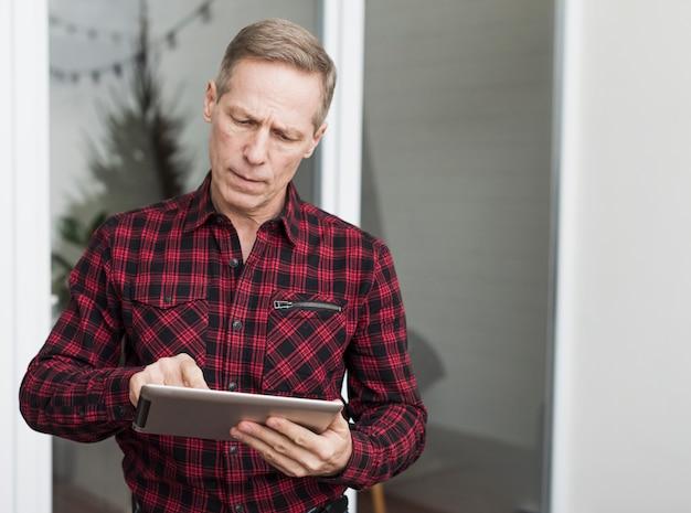 Starker älterer mann, der auf seiner tablette schaut Kostenlose Fotos