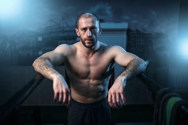 Starker athlet auf gymnastikstangen im fitnessstudio Premium Fotos