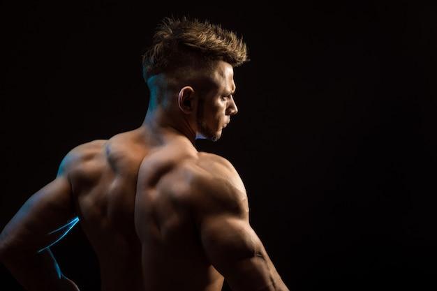 Starker athletischer eignungs-mann, der rückenmuskulatur, trizeps, latissimus über schwarzem hintergrund aufwirft Premium Fotos