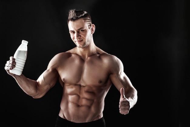 Starker athletischer muskulöser mann mit einer flasche Premium Fotos