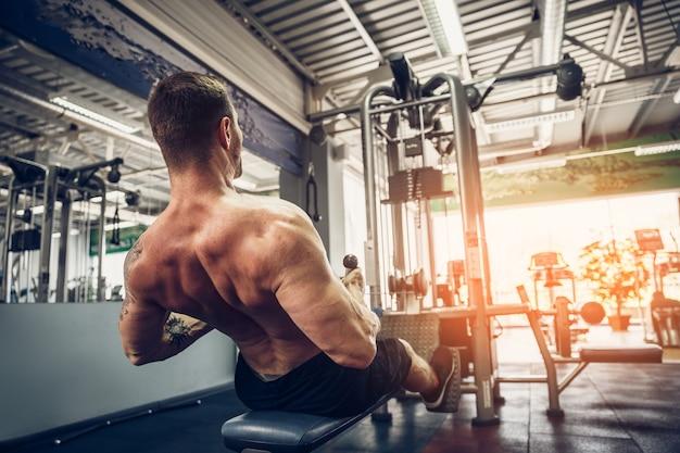 Starker bodybuilder, der schwergewichts- übung für rückseite auf maschine tut Premium Fotos