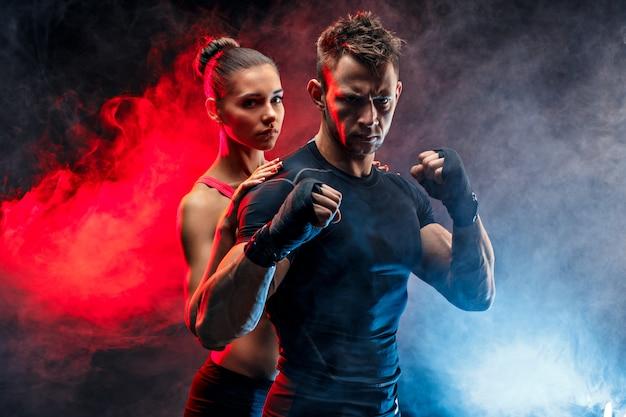 Starker boxer in haltung mit handwickeln auf seinen fäusten mit der freundin, die hinter ihm steht. Premium Fotos